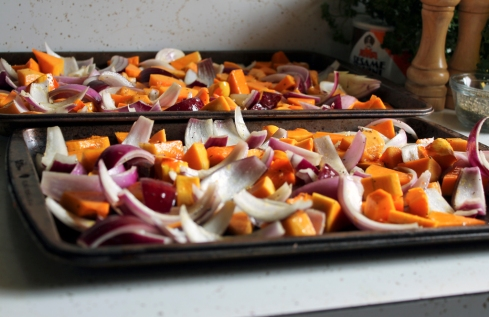 winter squash and red onions on baking sheets